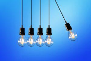 Fünf aneinandergereihte hängende Glühbirnen als Kugelstoßpendel